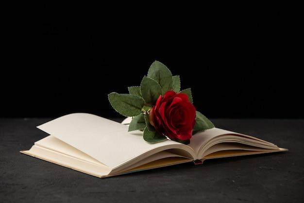 Vista frontale della rosa rossa con libro aperto su nero