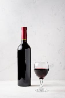 Vista frontale bottiglia di vino rosso accanto al vetro