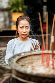 Vista frontale della donna religiosa con bruciare incenso al tempio