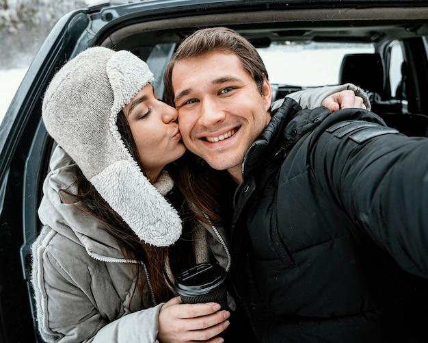 Vista frontale della coppia romantica prendendo selfie durante un viaggio su strada