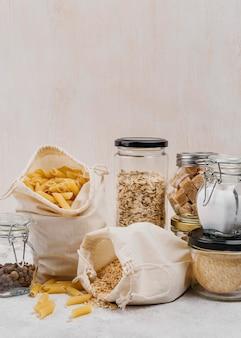 Vista frontale sacco di pasta e ingredienti in barattoli