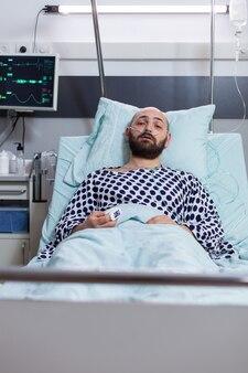 Vista frontale di un uomo malato triste con tubo di ossigeno nasale con malattia respiratoria che riposa a letto durante il trattamento terapeutico