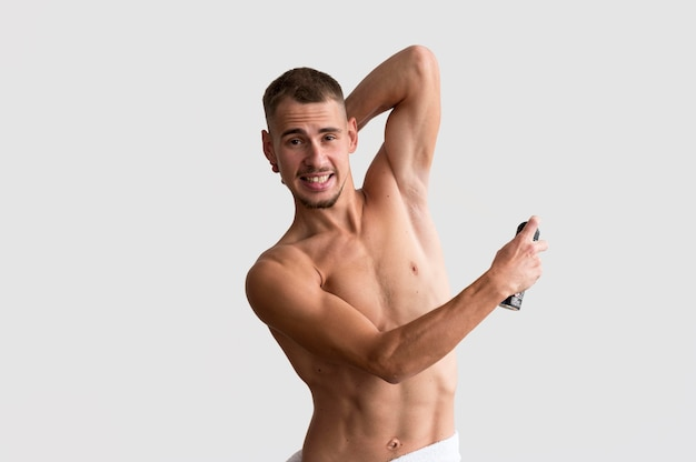 Vista frontale dell'uomo senza camicia che applica deodorante