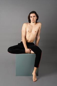 Vista frontale dell'uomo senza camicia che posa sul cubo