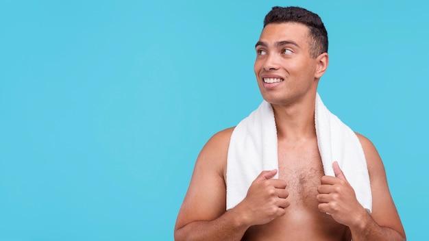 Vista frontale dell'uomo senza camicia che posa con l'asciugamano intorno al collo e lo spazio della copia