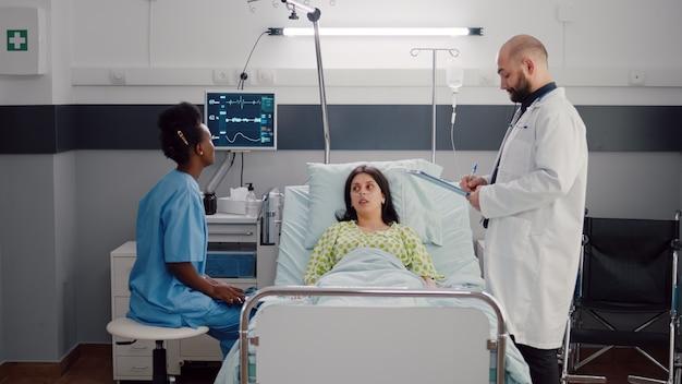 Vista frontale della donna malata sdraiata sul letto mentre un'infermiera afroamericana analizza le ossa dei raggi x