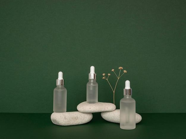 Disposizione dei contagocce dell'olio della pelle di vista frontale con le pietre