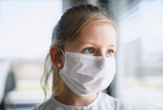 Vista frontale di una bambina con maschere facciali in casa, virus corona e concetto di quarantena.