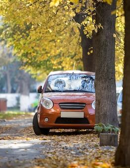 Vista frontale della piccola mini auto arancione parcheggiata in cortile tranquillo nella soleggiata giornata autunnale su edifici sfocati e grandi alberi secolari sfondo dorato fogliame bokeh. trasporto, concetto di problemi di parcheggio.