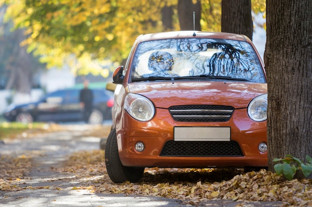 Vista frontale della piccola mini automobile arancione parcheggiata nel cortile tranquillo sulla soleggiata giornata autunnale su edifici sfocati e grandi alberi secolari fogliame dorato sfondo bokeh di fondo.