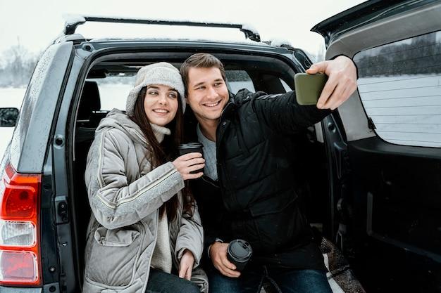Vista frontale delle coppie di smiley che prendono selfie durante un viaggio su strada
