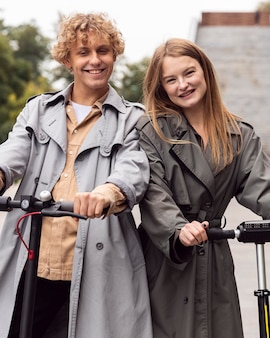 Vista frontale della coppia sorridente utilizzando scooter elettrico all'aperto
