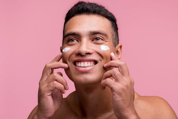 Vista frontale dell'uomo sorridente che applica la crema sul suo fronte