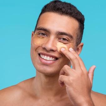 Vista frontale dell'uomo di smiley che applica le bende sull'occhio