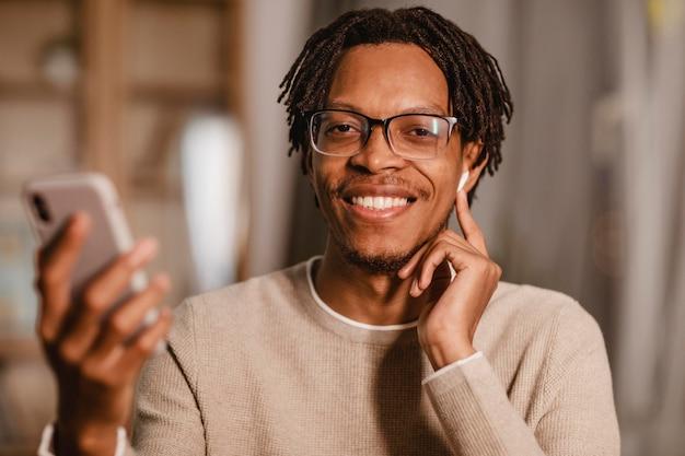 Vista frontale dell'uomo sorridente utilizzando i suoi auricolari e smartphone a casa