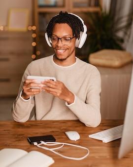 Vista frontale dell'uomo sorridente utilizzando le cuffie e lo smartphone a casa