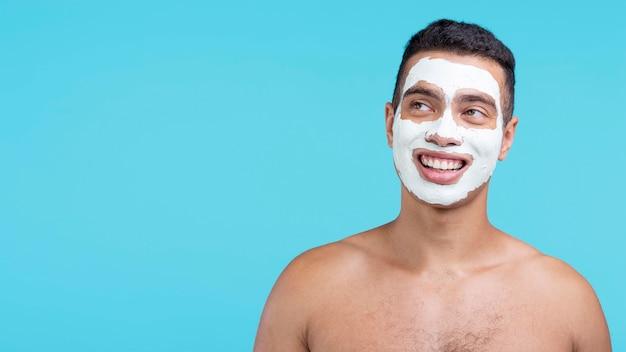 Vista frontale dell'uomo sorridente con la maschera di bellezza e lo spazio della copia