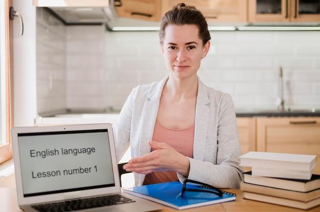 Vista frontale dell'insegnante di smiley che posa con il computer portatile e i libri per classe online