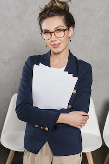 Vista frontale della donna di smiley dalle risorse umane in possesso di documenti