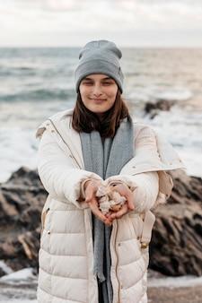 Vista frontale della donna sorridente con conchiglie