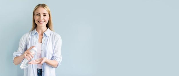 Vista frontale della donna di smiley usando disinfettante per le mani Foto Premium
