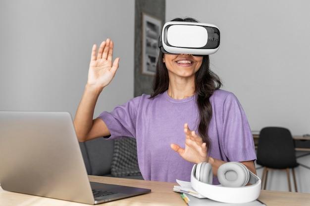 Vista frontale della donna sorridente utilizzando le cuffie da realtà virtuale a casa con il computer portatile