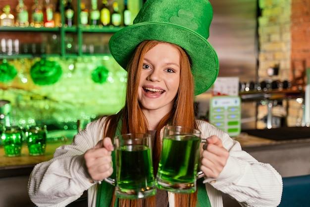 Vista frontale della donna sorridente con il cappello che celebra st. la giornata di patrick al bar
