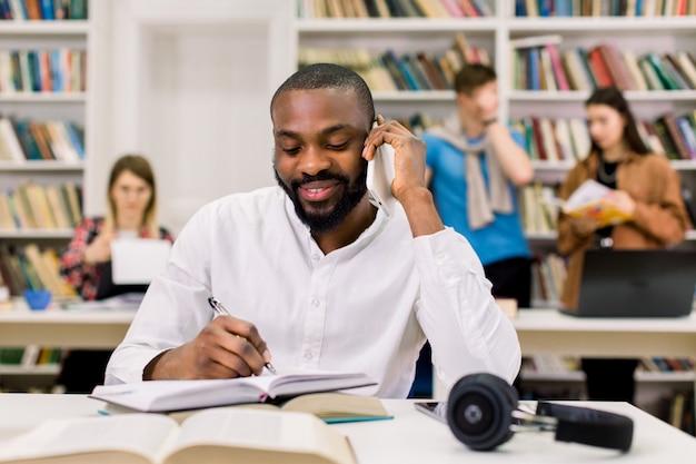 Vista frontale del giovane africano sorridente in camicia bianca, parlando su smartphone e scrivere note, mentre studiava e preparava per l'esame o il test nella biblioteca universitaria