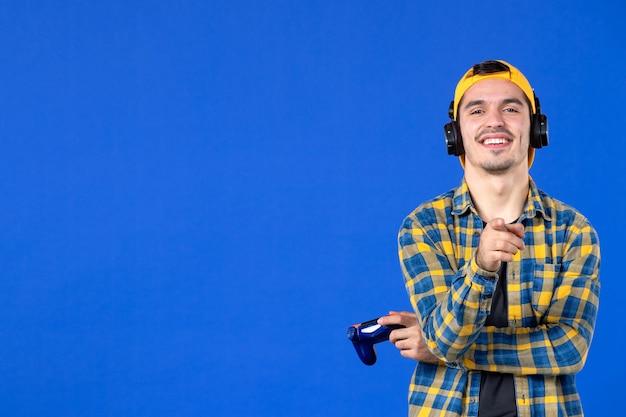 Vista frontale del giocatore maschio sorridente con gamepad che gioca al videogioco sulla parete blu
