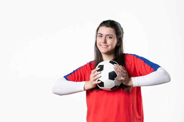 Vista frontale sorridente giovane femmina in abiti sportivi con pallone da calcio