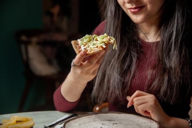 La vista frontale di una giovane donna sorridente che mangia una fetta di pizza deliziosa consuma fast food