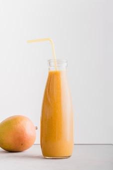 Bottiglia di frullato vista frontale con paglia e mango