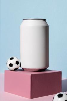 Vista frontale della lattina di soda con palloni da calcio