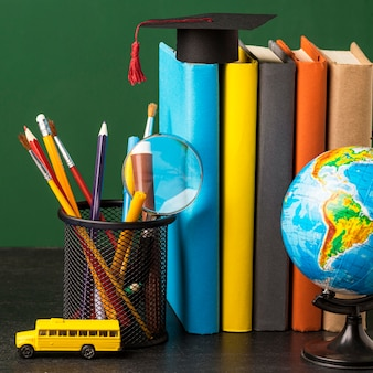 Vista frontale della pila di libri con cappuccio accademico e globo