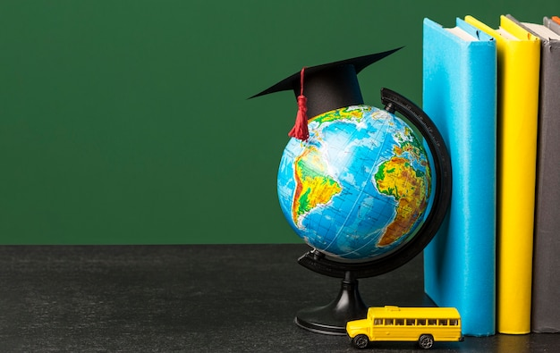 Vista frontale della pila di libri con cappuccio accademico e scuolabus