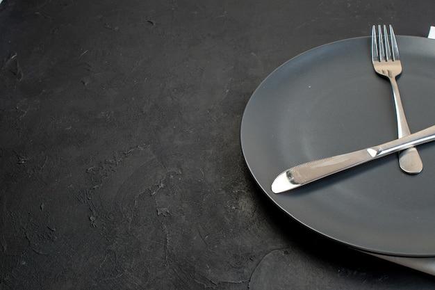 Vista frontale di posate in acciaio inossidabile su una piastra nera su sfondo di colore scuro con spazio libero