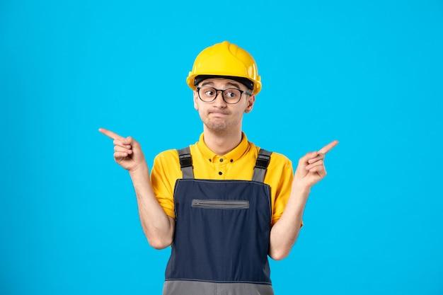 Vista frontale ha sottolineato il lavoratore di sesso maschile in uniforme su un blu