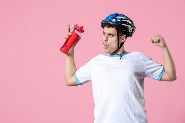 Vista frontale forte atleta maschio in abbigliamento sportivo con casco e bottiglia d'acqua