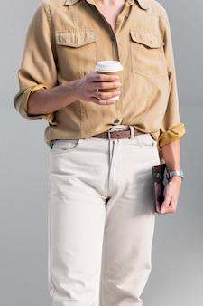 Vista frontale dell'uomo alla moda che propone all'aperto mentre si tiene compressa e tazza di caffè