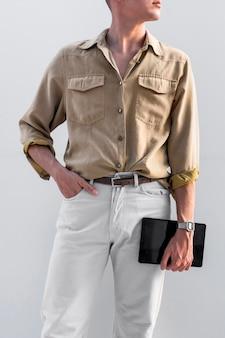 Vista frontale dell'uomo alla moda che propone all'aperto mentre si tiene la compressa