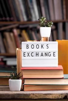 Vista frontale di piante grasse e libri con copertina rigida in biblioteca con scatola luminosa