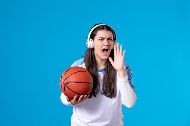 Vista frontale parlando giovane femmina con le cuffie tenendo la pallacanestro