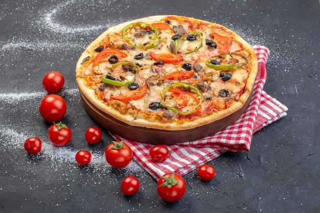 Pizza gustosa vista frontale con pomodori rossi su superficie scura