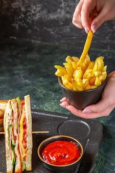 Vista frontale gustosi panini al prosciutto con patatine fritte superficie scura