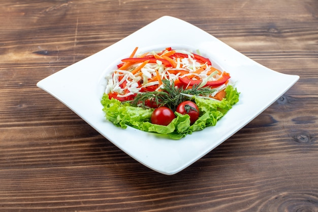 Vista frontale gustosa insalata di verdure con insalata verde e cavolo all'interno della piastra sulla superficie marrone