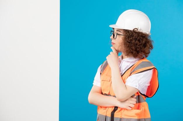 Costruttore femminile di pensiero di vista frontale in uniforme sulla parete blu