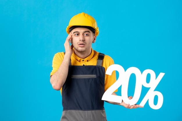 Vista frontale del lavoratore maschio di pensiero in uniforme con la scrittura sull'azzurro
