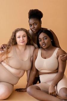 Vista frontale di tre donne in shaper del corpo di illusione nuda che propongono insieme