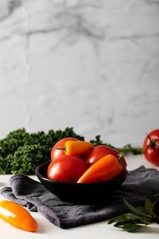 Pomodori e peperoni di vista frontale in ciotola con il canovaccio da cucina