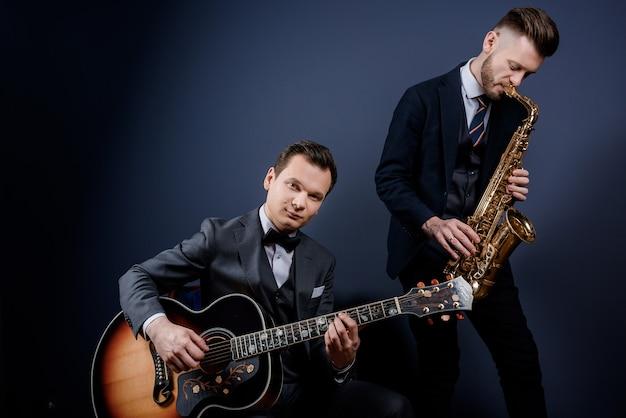 Vista frontale di due uomini che suonano la chitarra e il sassofono sulla parete blu isolata